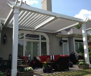 Less angled view of white traditional pergola over red-cushioned patio furniture