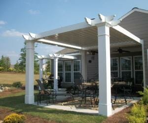 Attached white and gray pergola sitting over cement slab patio with outdoor furniture
