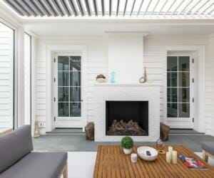 White house with outdoor patio covered by a louvered roof pergola that is protecting a gray couch, wood slat coffee table and outdoor fireplace