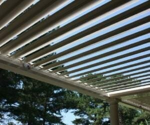 Detail of pergola louvers with green trees and blue sky peeking through