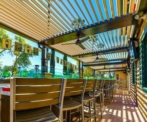 Long row of slat-back chairs is juxtaposed with vibrant blue and green landscape as seen through open pergola louvers bathed in golden light