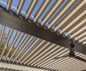 Close-up looking through pivoting louvers of Pergola X with fan attached to beam and blue sky and hint of tree leaves beyond