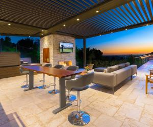 Adjustable-louvered-pergola covered patio at sunset with stylish outdoor furniture and mounted flat screen TV