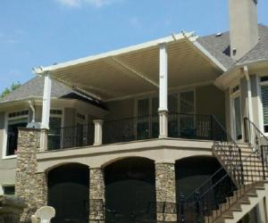 Tan two-story house with white pergola over second level patio deck supported by stone pillars