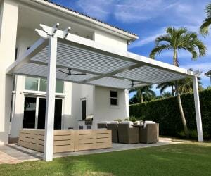 White pergola in backyard of a modern white home with green grass, palm trees, and chunky patio furniture