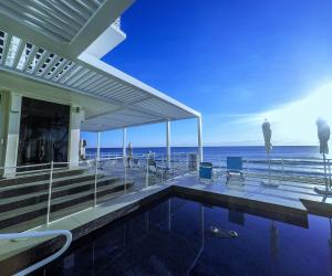 Contrasting white pergola next to deep blue pool looking out to ocean