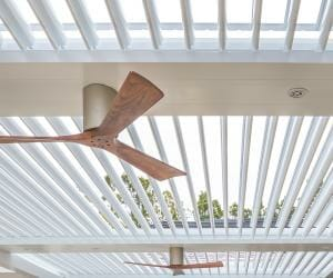 Close-up detail of white pivoting louvers in pergola with two wood tone fans affixed to beams