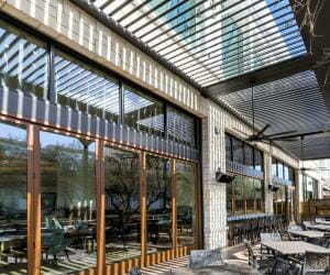 Outdoor restaurant patio covered by a StruXure pergola, with louvers opened and reflecting in glass facade