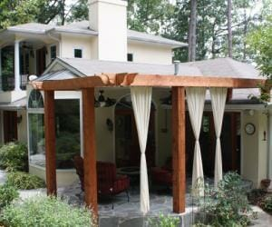 Wooden pergola with white curtains covering patio of traditional white house