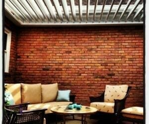 Patio furniture in front of red brick wall with open pergola louvers above