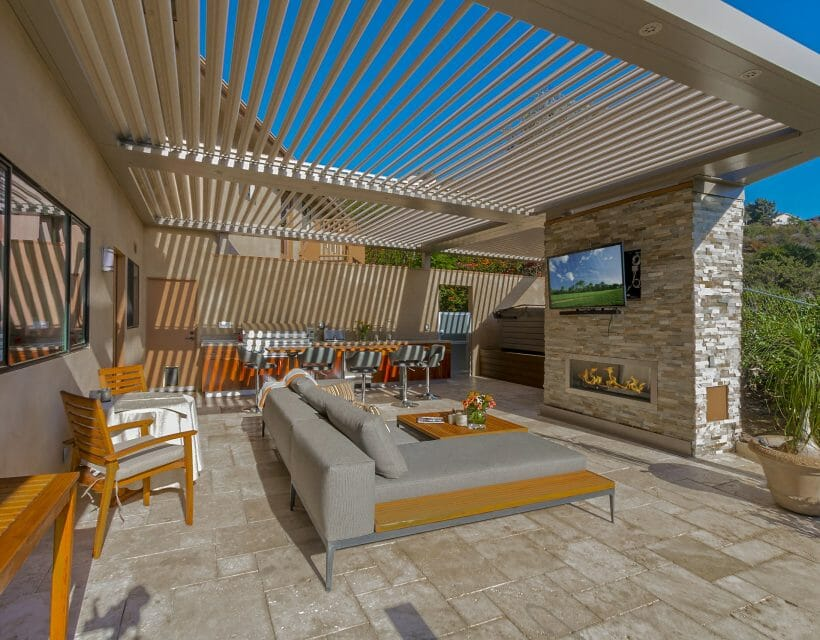 Beige stone tile patio with gray and wood outdoor furniture stacked stone fireplace under beige pergola with louvers open