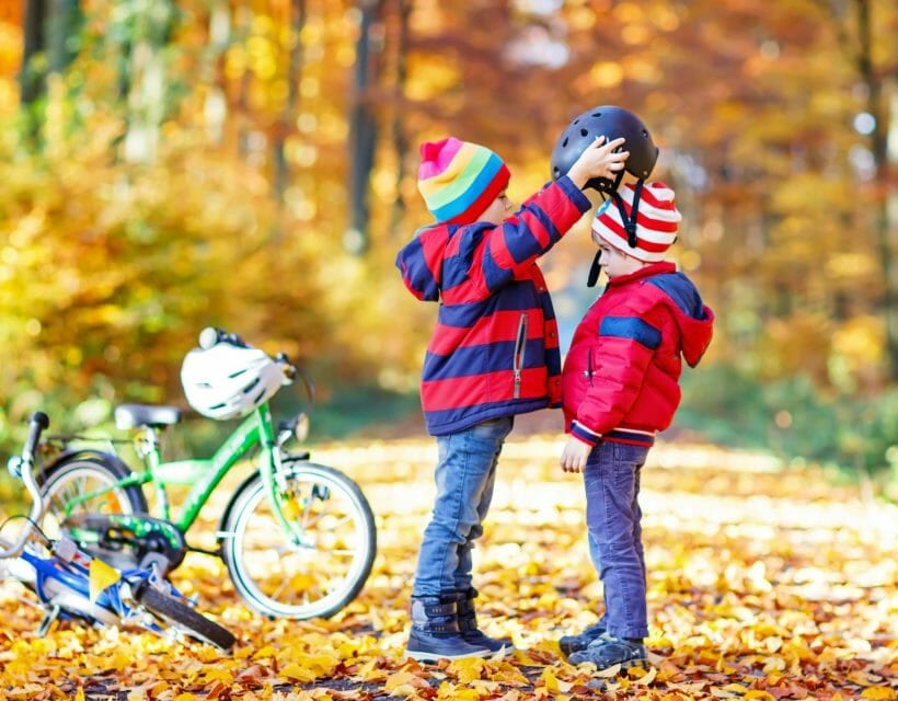 Young children with bikes and helmets standing on golden leaf path