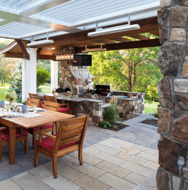 Stone outdoor fireplace and outdoor kitchen provides interest under white pergola with adjacent wood ceiling