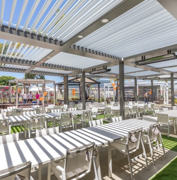 Expansive white pergola over long white tables and white chairs with green turf separating table and orange balloons scattered around space