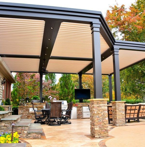 Bronze five-louver-zone pergola with beige louvers on stacked stone bases to match stairs leading up to house