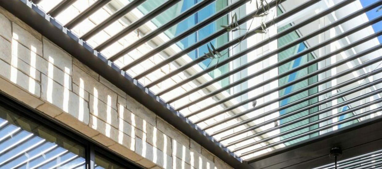 Alternate detail of open bronze pergola louvers with attached building materials in full view including patchwork stone and glass
