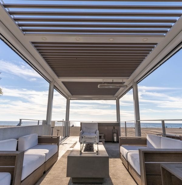Linear view of outdoor furniture under pergola overlooking sandy beach