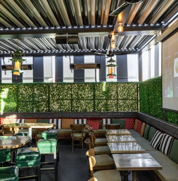 Outdoor space at restaurant has green leather backless stools yellow chairs colorful pillow along bench seating under black and white louvers