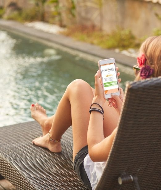 Girl with red flower in hair sitting on brown woven outdoor chaise looking at iPhone with StruXure app on it