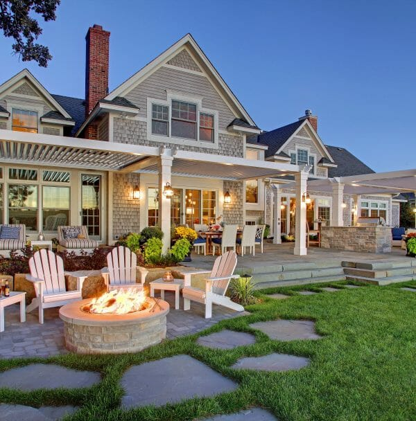 Enhanced green grass with lit fire pit traditional gray house with white trim and two white pergolas equals a perfect backyard setting