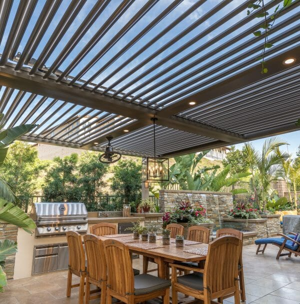 Adobe pergola with lights sits above tan stone paver patio with wooden outdoor furniture and built in grill