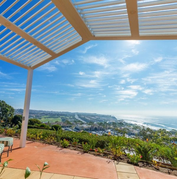 Hillside view down to ocean from terra-cotta patio covered by angled white metal pergola