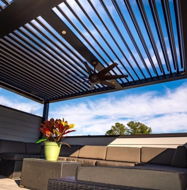 Looking up from brown outdoor furniture through open bronze pergola louvers with fan and red leafy plant in yellow-green pot