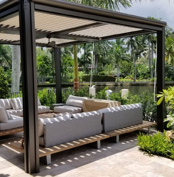 Free standing bronze pergola with tan louvers with neutral toned cushioned outdoor furniture surrounded by green plants on beige stone patio next to waterway