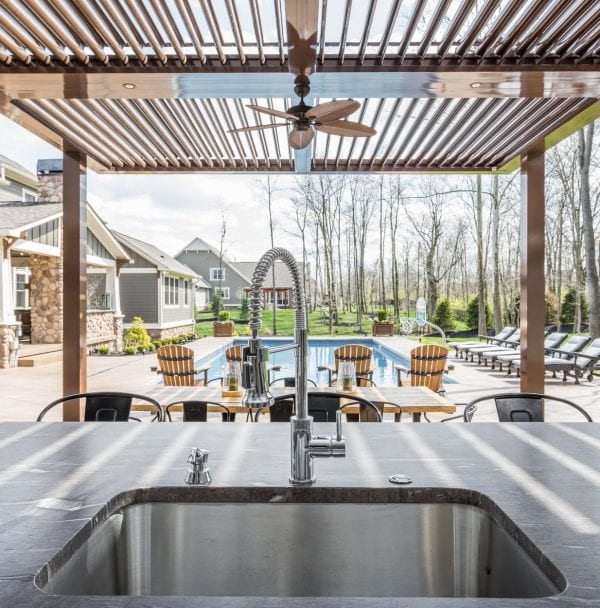 View from outdoor kitchen sink looking under bronze pergola with open pivoting louvers out to pool surrounded by chairs on pool deck and adjacent green lawn