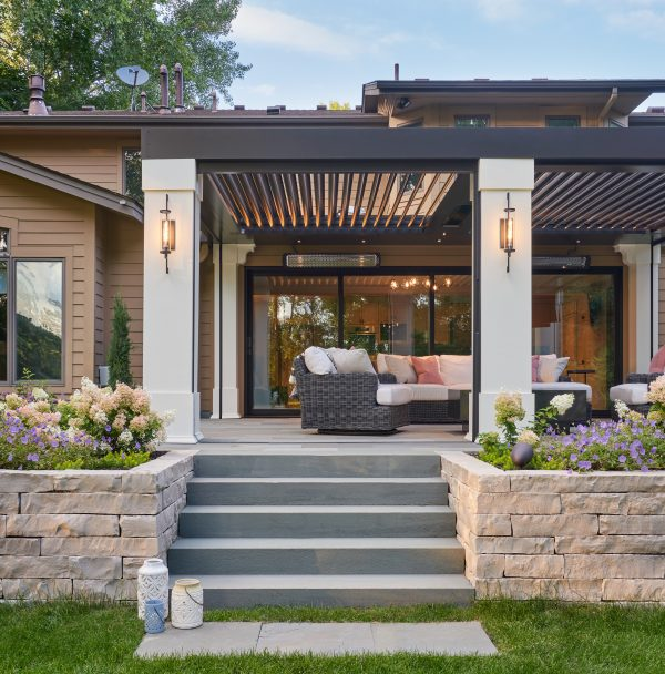 Gray steps between stacked stone garden zones lead to outdoor patio under bronze pergola with mounted TV