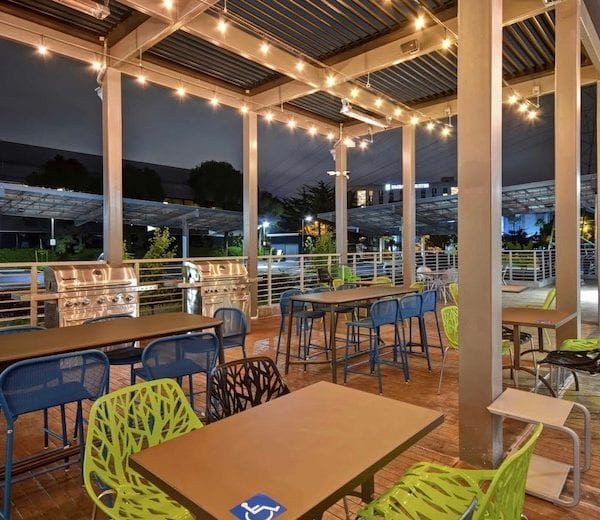 At night a beige pergola with closed bronze louvers is accessorized with rows of small lights that hang over dining deck with intermittent lime green chairs