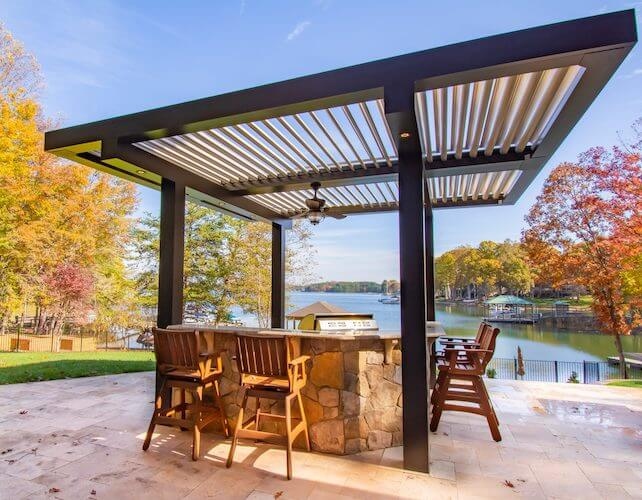 Lakeside black pergola with tan louvers covers outdoor grill and rock-clad dining bar with autumn foliage