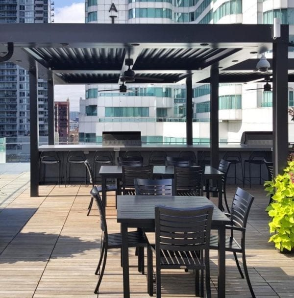 Black pergola on rooftop deck with black tables and chairs a black bar with grills and vibrant green plants spilling out of black planters