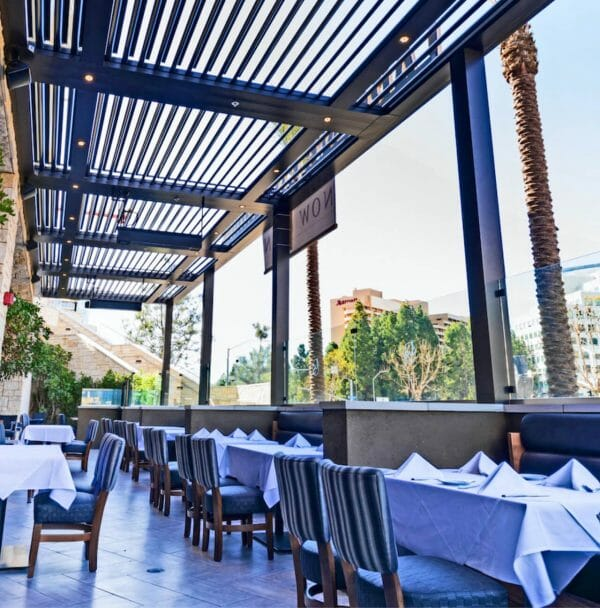 Outdoor restaurant seating with white tablecloths and striped upholstered chairs under open louver bronze pergola