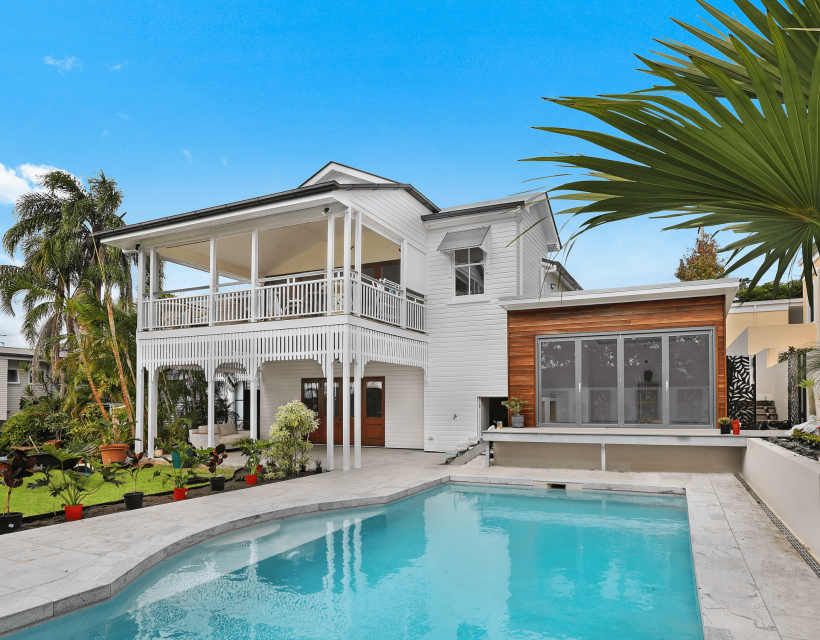 Turquoise blue pool in foreground and 2-story white house with single level wood clad add-on in background and tropical landscaping framing view