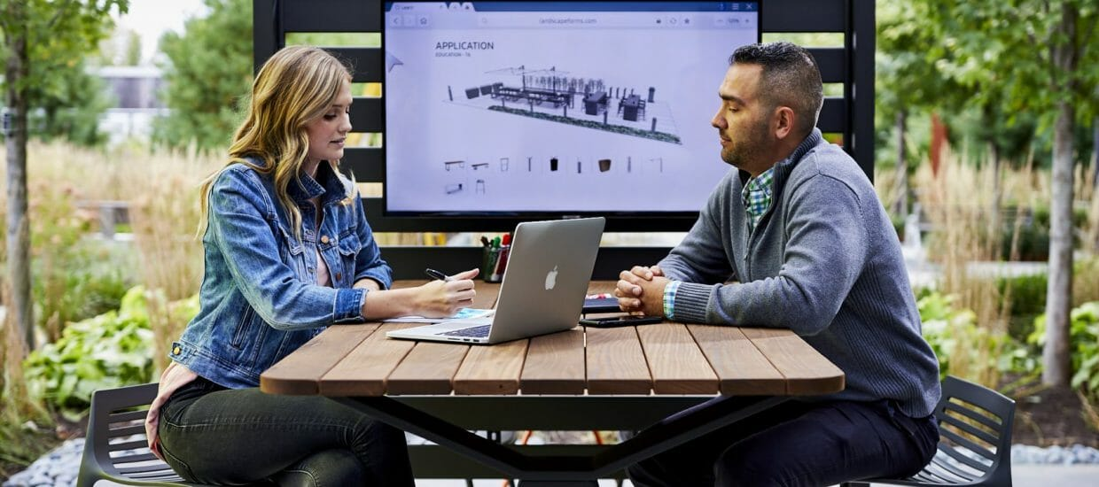 Woman and man seated at tall wood and metal outdoor table under opened pergola louvers with laptop on table and rendering mounted on back metal slatted wall