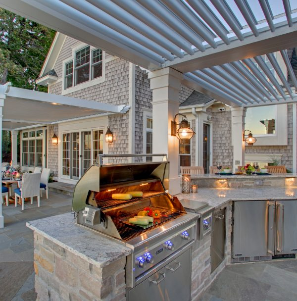 Outdoor kitchen with corn on the cob cooking on grill in foreground an white dining furniture with blue cushions under second pergola in background