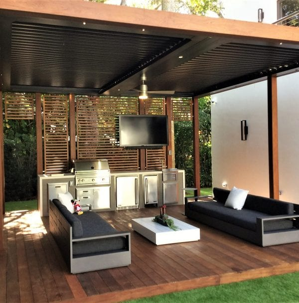 Wood patio platform with wood clad pergola frame and bronze louvers with back slatted feature wall that supports silver outdoor kitchen appliances and a flat screen TV
