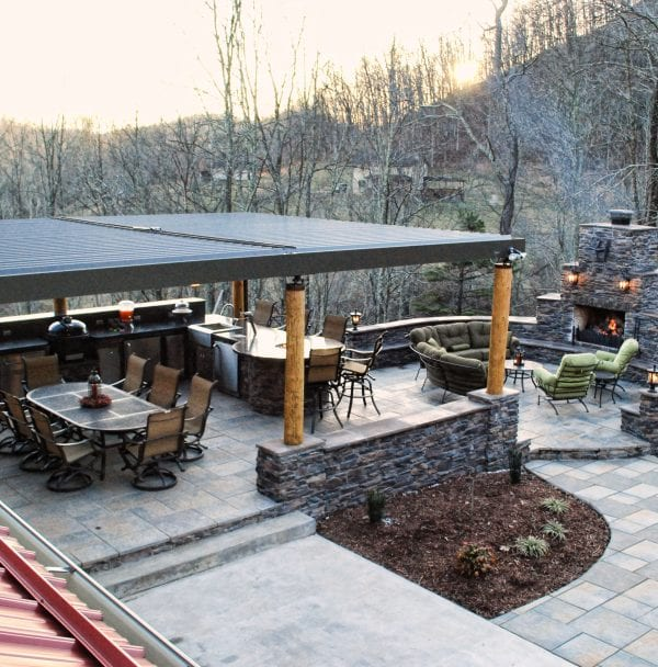 Just beyond red corrugated roof lays a stone paver patio covered by bronze louvered pergola on wooden support poles