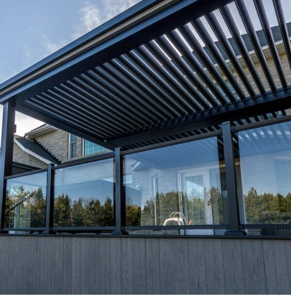 Standing outside home property with black pergola above patio that is visible through glass panels