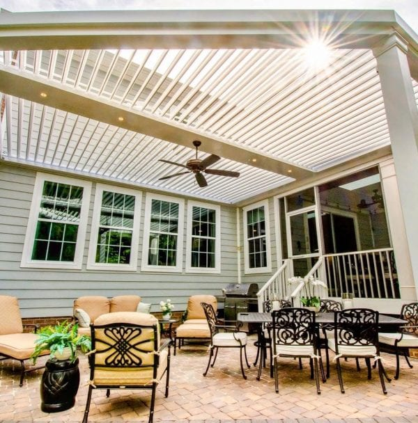 White pergola over brick patio with wrought iron furniture