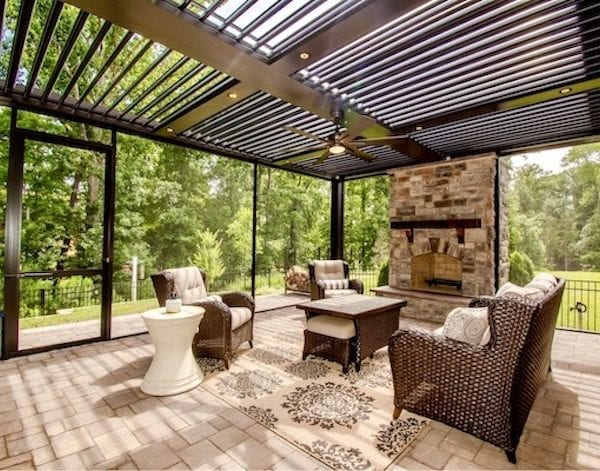 Color corrected view of bronze pergola with stone fireplace and surrounding screens