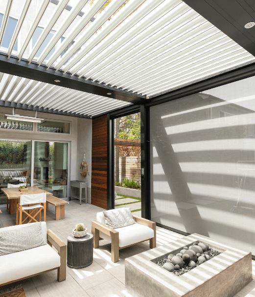 Black pergola frame with white louvers over neutral colored patio and outdoor furnishings