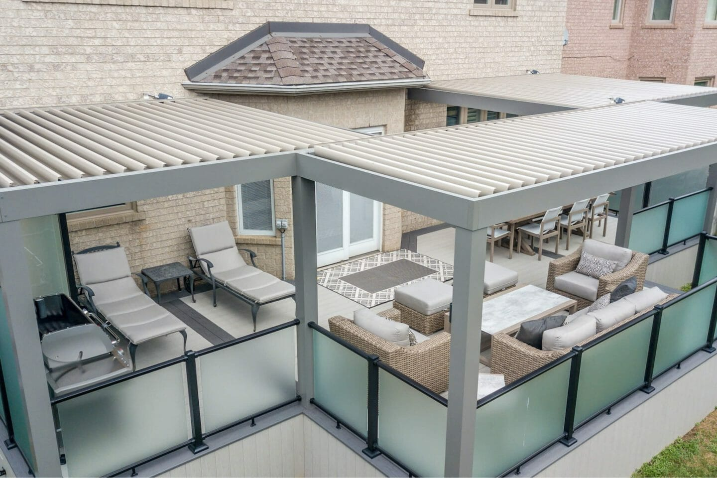 Looking down on three beige and gray patio structures with low green glass partitions