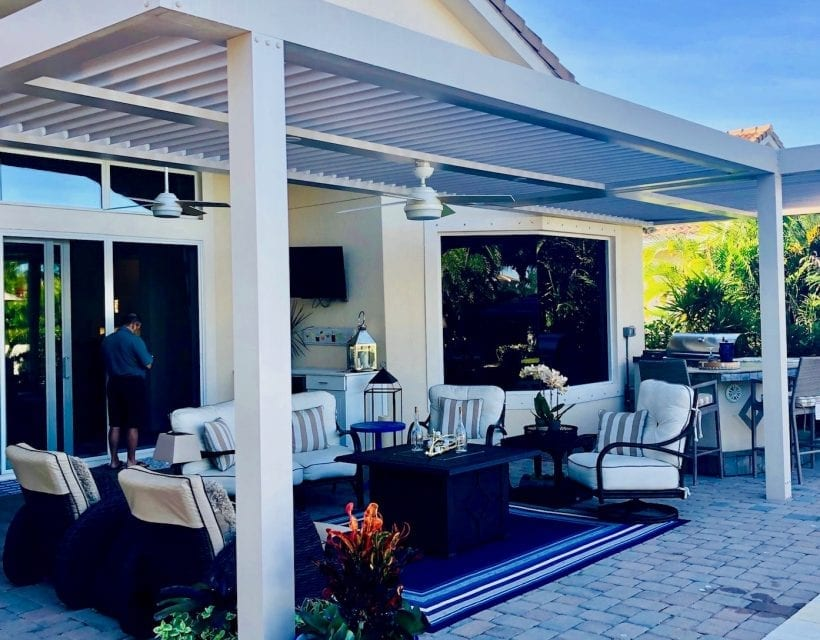 White pergola covered brick paver patio with luxury outdoor furnishing and blue statement rug with man standing at sliding glass door leading into house