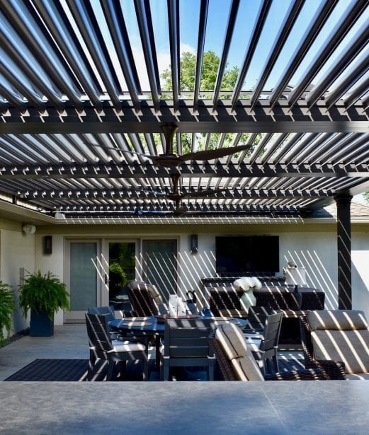 Bronze Pergola X with pivoting louvers opened over gray patio with white flowers in vase