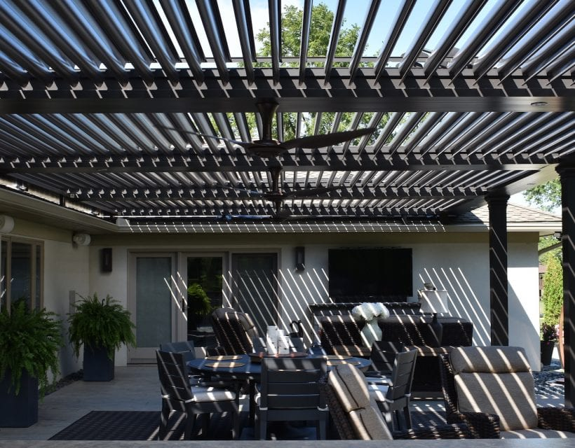 Close-up of backyard patio covered by bronze pergola with pivoting louvers and fan and sky view revealed between open louvers