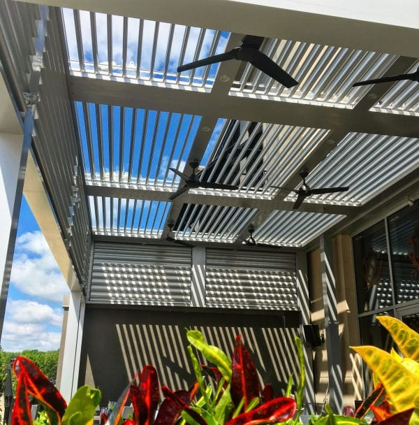 Red, yellow and green plants in foreground looking up at opened metal pergola louvers with size fans