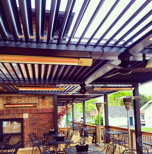 Restaurant outdoor deck with black metal tables and chairs under bronze pergola louvers opened with heaters attached