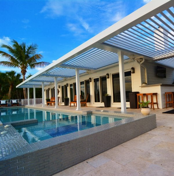 Blue sky and palm trees over opened louvers of white pergola with pool just steps away